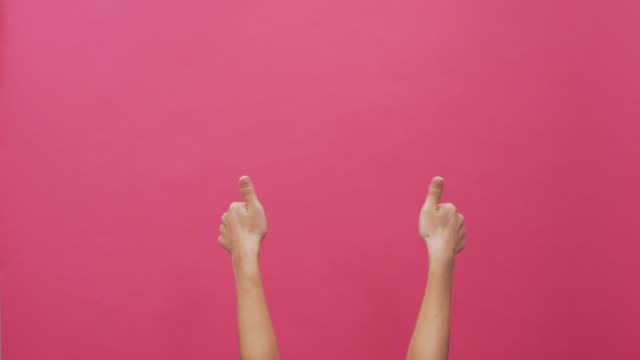 Woman thumb up on isolated pink background 4k