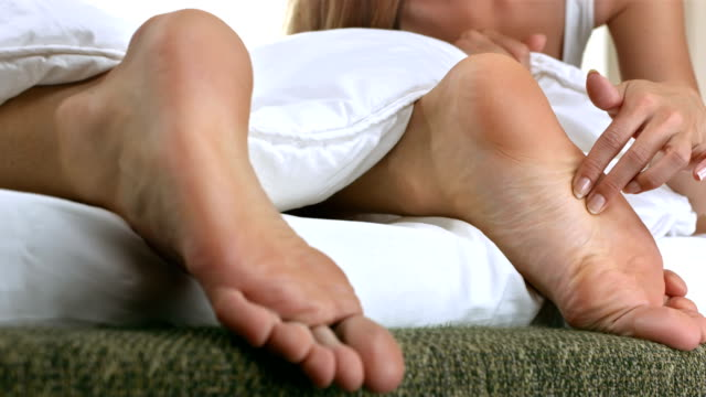 hd: donna fare il solletico i piedi del suo ragazzo - fare il solletico video stock e b–roll