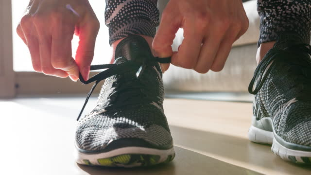vídeos de stock e filmes b-roll de woman tightening the knot on her sports shoe, getting ready for morning run - feet hand