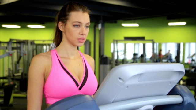Woman tired walking on a treadmill in gym video