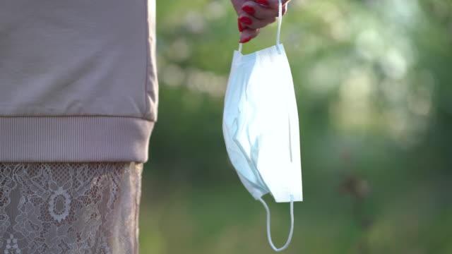 女性は彼の医療マスクを脱いで新鮮な空気を吸い、検疫後に自由を楽しんでいます。 ビデオ