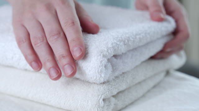 vidéos et rushes de une femme touche une serviette blanche fraîche - peignoir