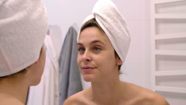 Woman touching her face and looking in the mirror after shower