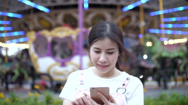 Woman touching smartphone on the amusement park of