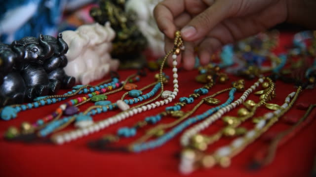 Woman tourist choosing a bracelet at souvenir shop in Thailand.