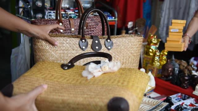 Woman tourist choosing a handmade bag at souvenir shop in Thailand.