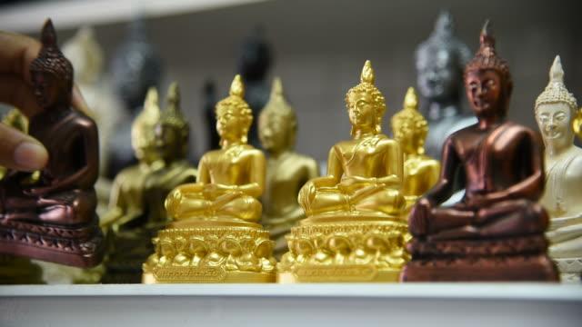 Woman tourist choosing Buddha at souvenir shop in Thailand.
