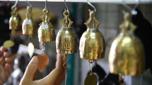 Woman tourist choosing the bells at souvenir shop in Thailand.
