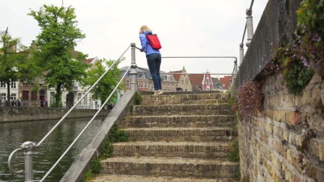 Woman Tourist Coming To Railing Of Embankment And Go Down The Stairs To River Mature caucasian tourist woman approaches the railing of canal embankment and descends the stairs to river of historically old stone town. 4k railing stock videos & royalty-free footage