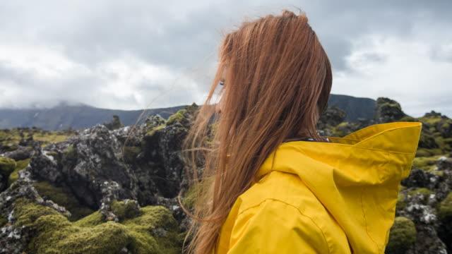 stockvideo's en b-roll-footage met vrouw toeristische verkennen van ijsland, mossy landschap te bewonderen - bewondering