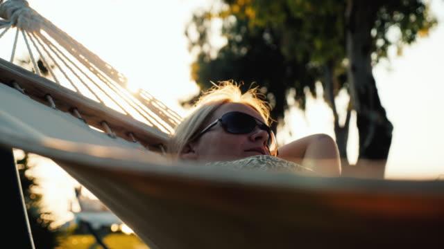 en kvinnlig turist i en sommarklänning slappnar av i en hängmatta. solen på horisonten skapar vackra höjdpunkter i ramen - endast unga kvinnor bildbanksvideor och videomaterial från bakom kulisserna