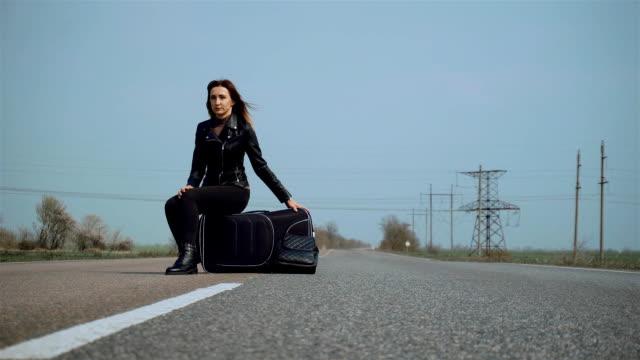 Kvinna turist sitter på hennes bagage i resväska på hjul i mitten av asfalt väg och väntar på att passera bil video