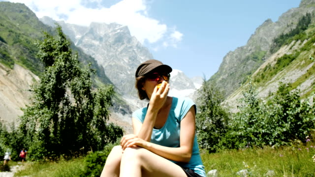 Woman tourist sits on a stone and eats a peach in a hike on the background of a beautiful mountain landscape Woman tourist sits on a stone and eats a peach in a hike on the background of a beautiful mountain landscape. peach stock videos & royalty-free footage