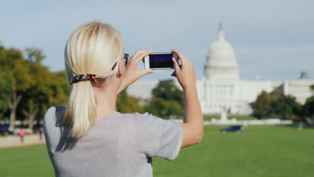 A woman tourist takes pictures of the Capitol building in Washington. Tourism in the USA concept