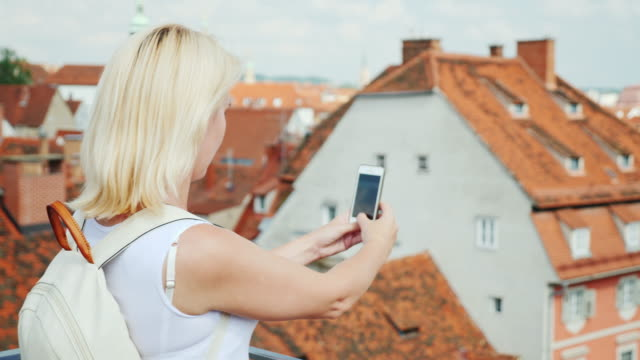 A woman tourist takes pictures of the old part of the beautiful city of Graz. In the picture are visible red tile roofs of the city and old houses. Tourism in Europe video