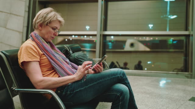 A woman, tourist, using a smartphone when she sitting and waiting for a departure in the airport lounge. Panning camera motion.