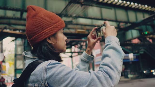 vídeos de stock e filmes b-roll de woman tourist using smartphone take a photo of new york city. - fotografar
