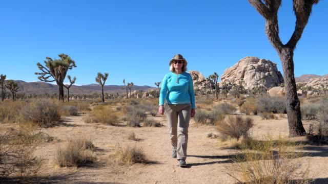 vidéos et rushes de femme touriste se promène à travers le désert au milieu des cactus, joshua tree et rochers - une seule femme d'âge mûr