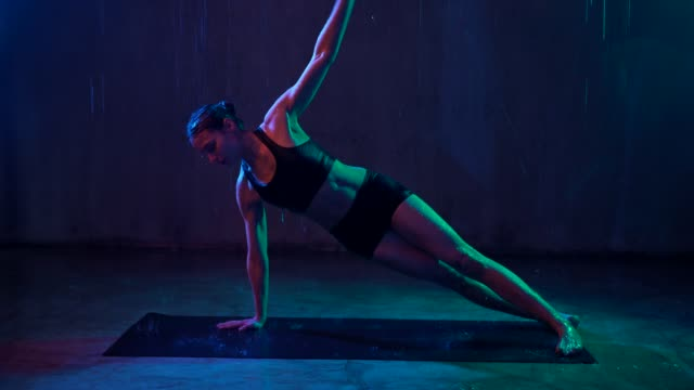 Woman training arms in plank position, rain.