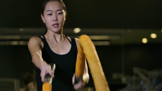 女性戦いロープ付きのジムでトレーニング。魅力的なアジアの女性の強力な戦闘スローモーションのジムでロープを使ってトレーニングを行います。 - 有酸素運動点の映像素材/bロール