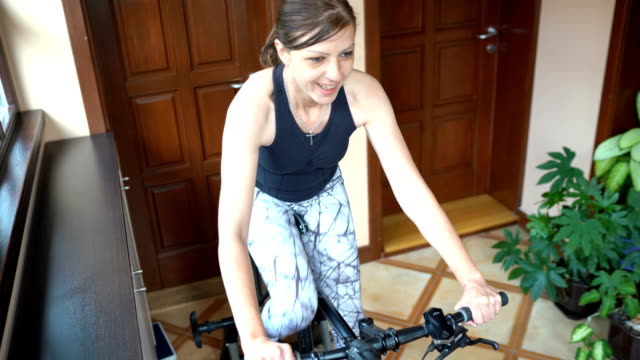 Woman training on cycle home trainer Woman training on cycle home trainer exercise bike stock videos & royalty-free footage