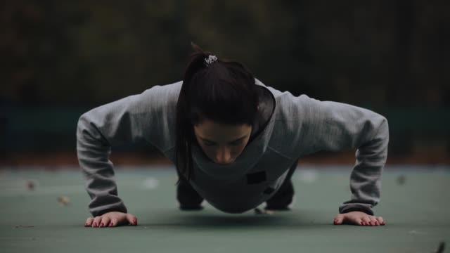 Woman training outdoor makes push-ups video