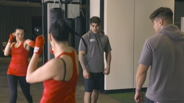 Woman training with coach in front of mirror video