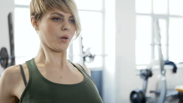 Woman traininig in the gym Young woman wearing sporty outfit is in the gym. Sporty young woman is near the training apparatus. Woman actively makes exercises for her back muscles. Young sporty female pulls the apparatus and breathes. human back stock videos & royalty-free footage