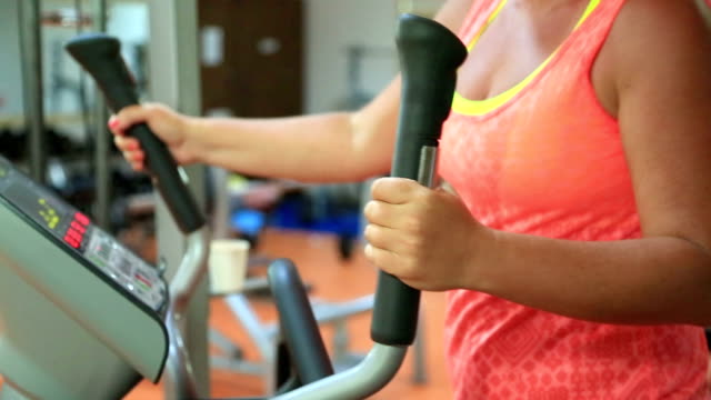 Woman trains on stepper machine in gym. Concept of health and fitness video