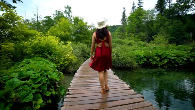 woman traveler enjoys waterfall in plitvice lakes - национальный парк плитвицкие озёра стоковые видео и кадры b-roll