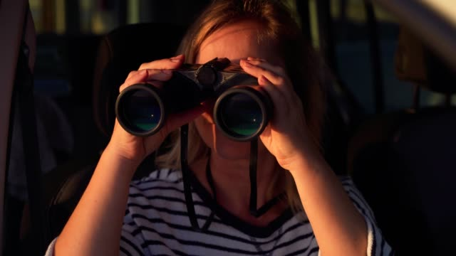 woman traveler looking through binoculars from a car window video