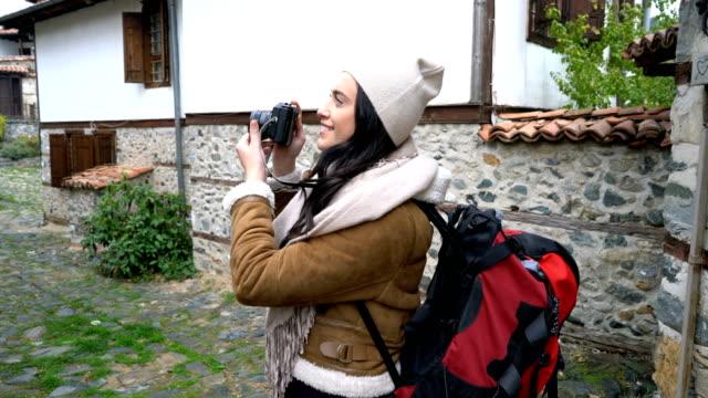 Viajante de mulher tirando fotos enquanto caminhava na pequena aldeia. - vídeo