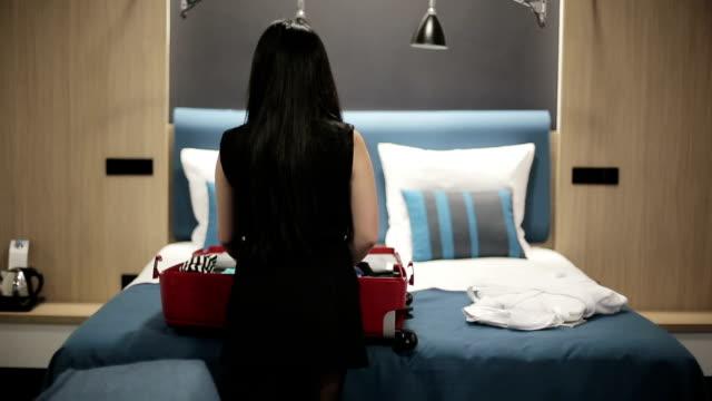 Woman traveler unpacking suitcase in hotel room video
