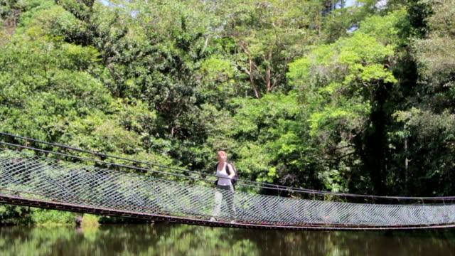Woman Traveler Walking over a Suspension Bridge, Borneo video