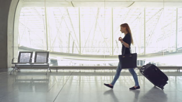 woman traveler with luggage walking through airport terminal - airports stock videos & royalty-free footage