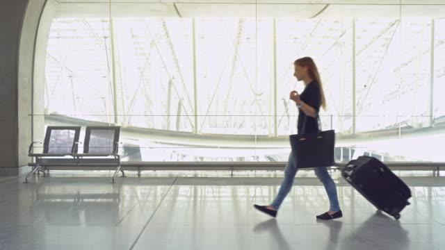 stockvideo's en b-roll-footage met vrouw reiziger met bagage luchthaventerminal doorlopen - zakenreis