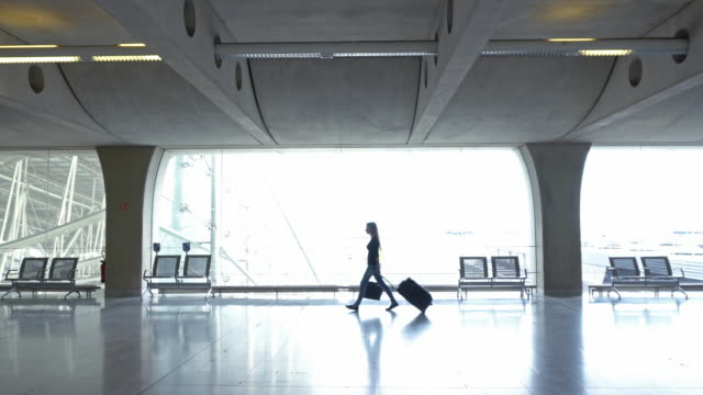 woman traveler with luggage walking through concourse - business travel stock videos and b-roll footage