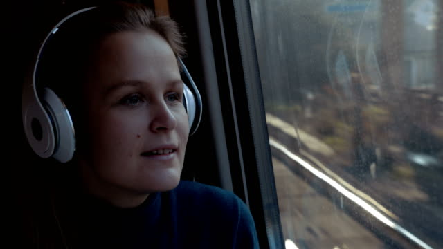 Woman traveling by train with favorite muisc Young woman in wireless earphones relaxing with music in the train. She singing song, dancing and enjoying scene from the window railroad station platform stock videos & royalty-free footage