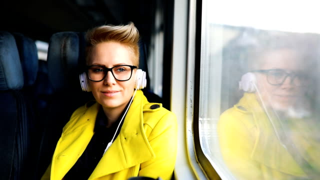 Woman traveling by train with favorite music Woman traveling by train with favorite music railing stock videos & royalty-free footage