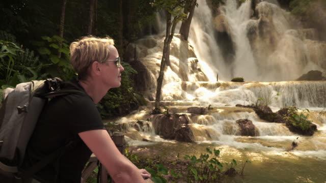 woman traveller at kuang si waterfall, luang prabang, laos - krótkie włosy filmów i materiałów b-roll