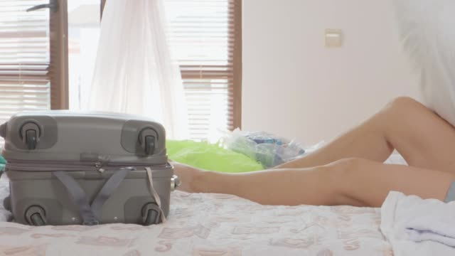 Woman traveller lying on the bed in the hotel room video
