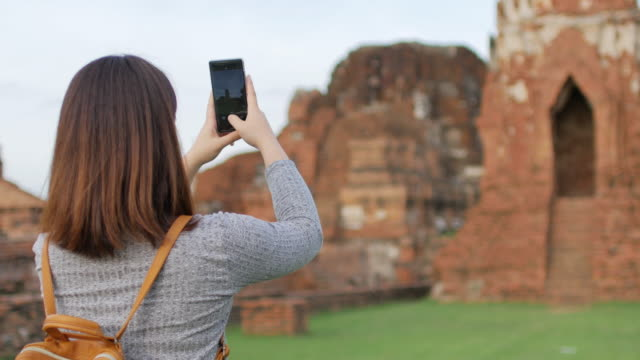 Woman traveller using mobile phone for take a photos at ayutthaya historical park Thailand video