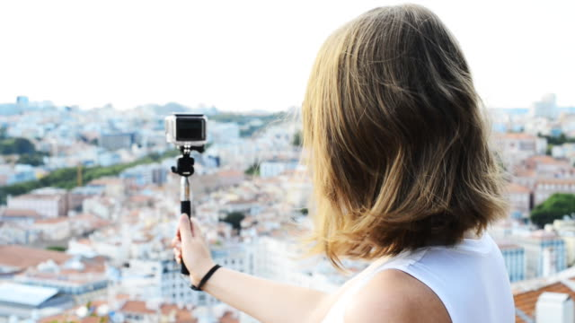 Woman traveller with camera shooting video. video