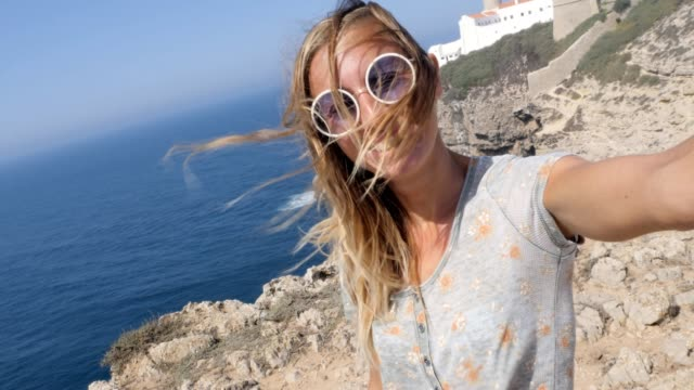Woman travelling in Sarges Portugal, takes a selfie with lighthouse in the background. Young female selfie with coastal views