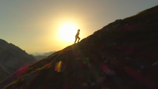 AERIAL SILHOUETTE: Woman trekker trying to reach mountain peak before sundown.