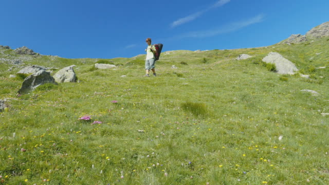 Woman trekking in idyllic mountain landscape on the Italian Alps, slow motion video