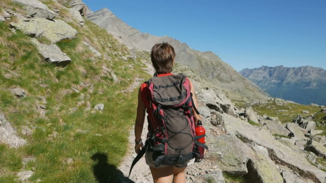 Woman trekking on the Alps, slow motion, rear view video