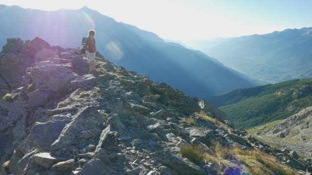 Woman trekking on the Italian French Alps, backlight video