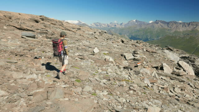 Woman trekking on the Italian French Alps, slow motion video