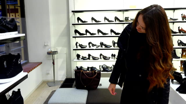 woman try on black sneakers in shoes store, stand in front of mirror - shoes fashion stock videos and b-roll footage